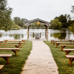 Wedding ceremony site by pond dock with walkway and benches at Civil War Ranch
