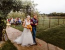 Smiling bride and groom after ceremony at outdoor wedding venue by pond
