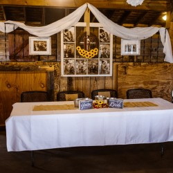Bride and Groom head table with sunflower decorations inside wedding barn at Civil War Ranch