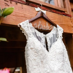 White wedding dress hanging on barn. Hangar has bride spelled out in wire.