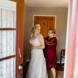 Grandmother helping bride put on wedding dress at Civil War Ranch