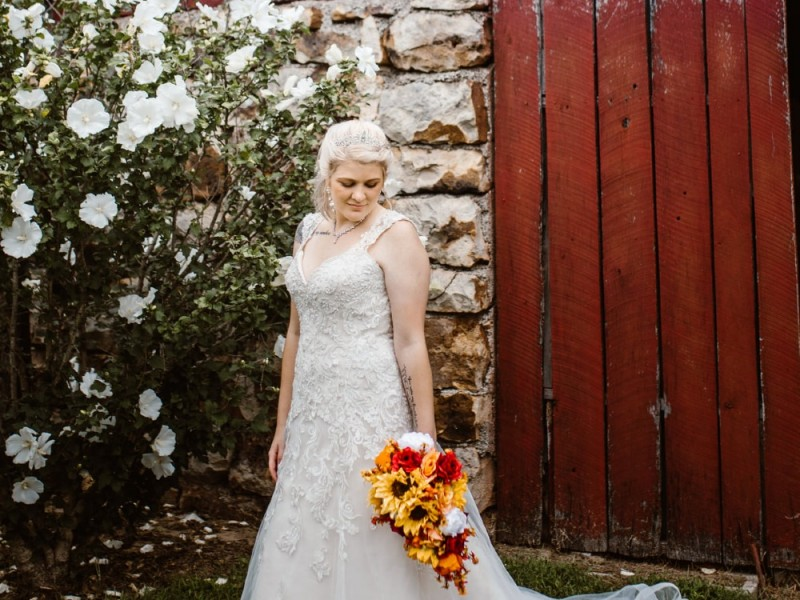 Bride in white dress with sunflower boquet in front of red barn at Civl War Ranch