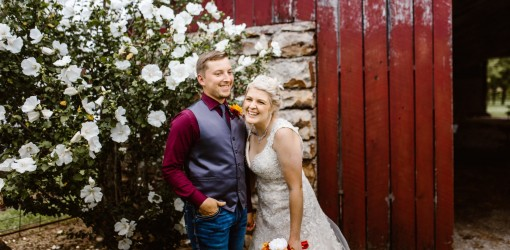 Laughing Bride and Groom in front of red barn and white flowers
