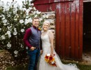 Smiling bride and groom in front of red barn and white flowers