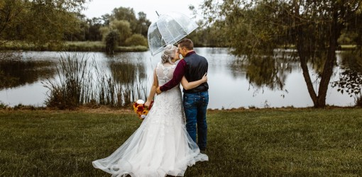 Bride and Groom under clear umbrella facing pond at Civil War Ranch