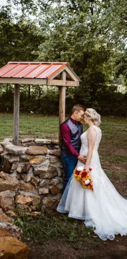Bride and Groom in front of the well at Spring Creek wedding ceremony site, Civil War Ranch wedding venue